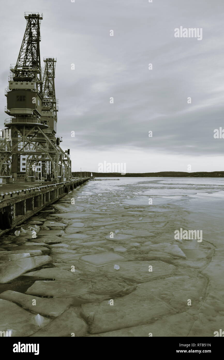 Ice floes are floating on an empty harbor bay in winter. Monochrome photograph,tones sepia and blue. - Stock Image