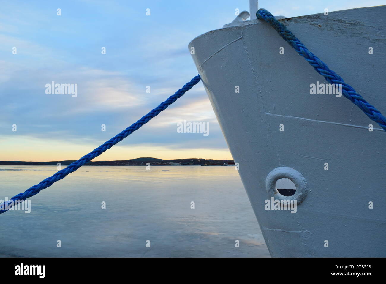 A ship lies moored in an ice covered harbor bay. Stock Photo