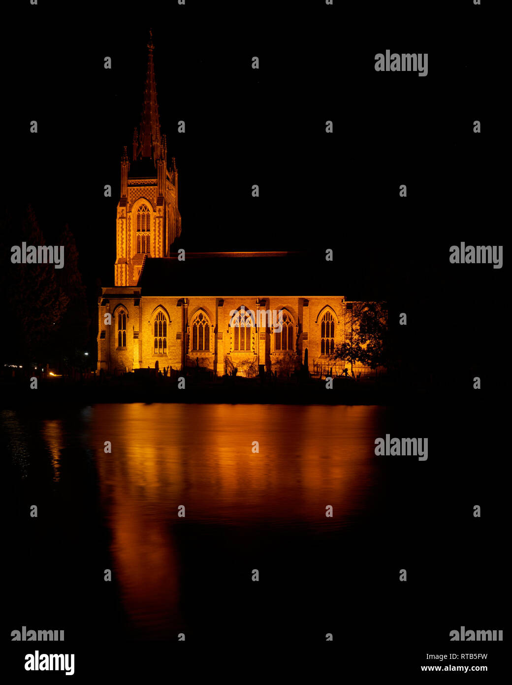 Spiritual All Saints Church at Marlow. Reflected in a flowing River Thames at night. - Stock Image