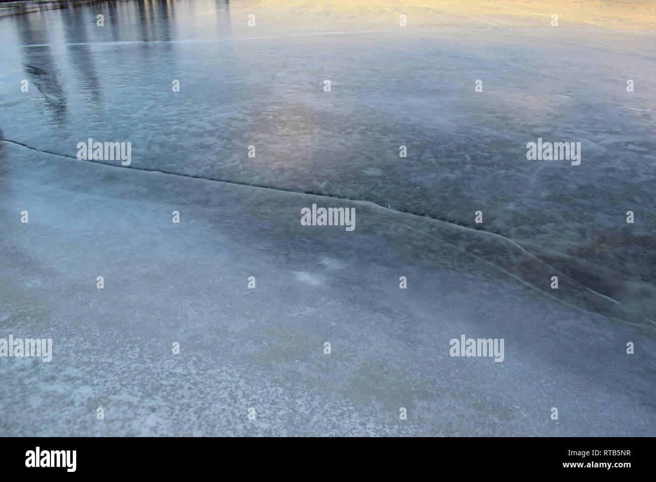 Ice covering a harbor bay in winter is shimmering in the light of the setting sun. Deep cracks are running through the ice. Stock Photo