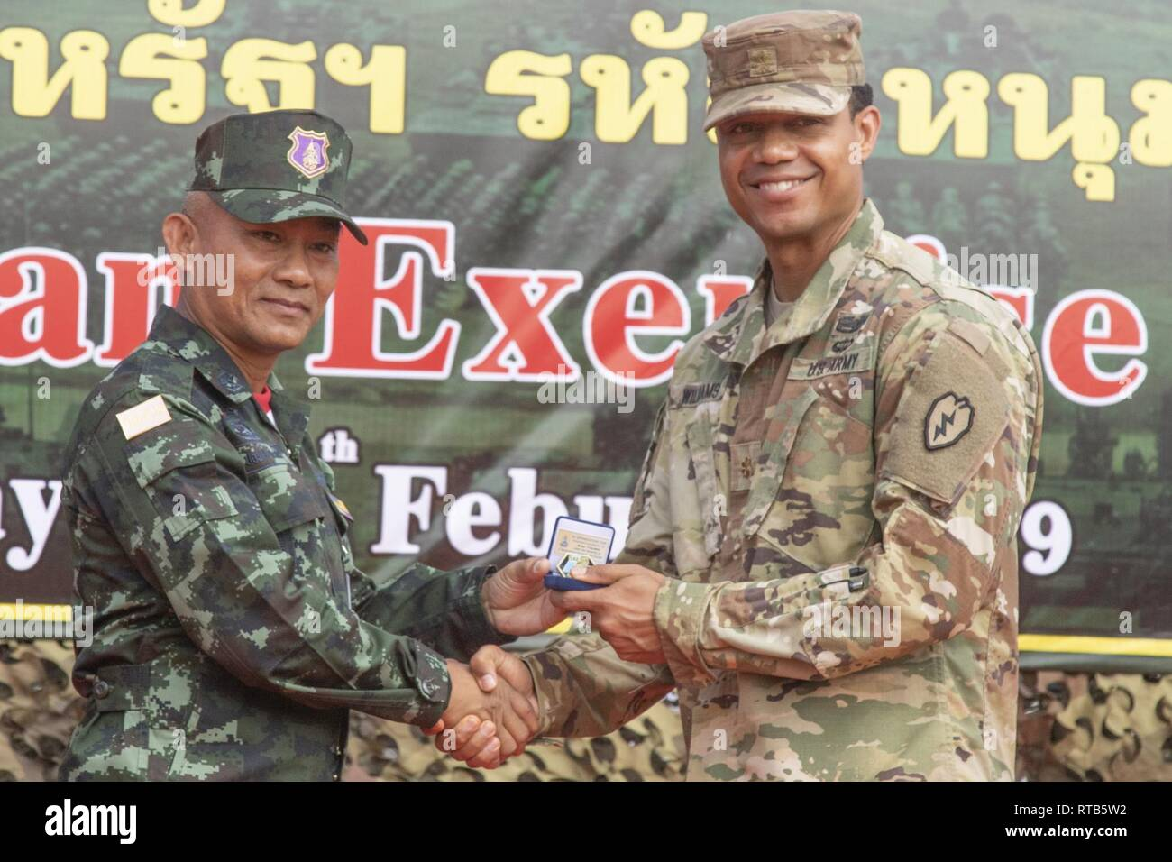 Chitsanupong Rodsiri, the Deputy Commanding General for 2nd Infantry Division King's Guard, Royal Thai Army, and Maj. Williams formally exchange gifts ...