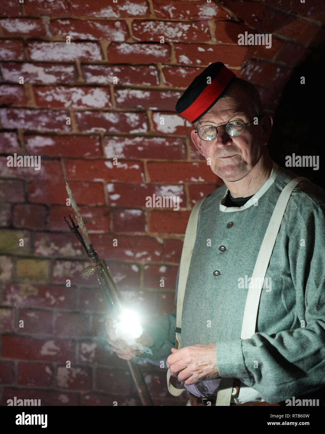 Victorian re-enactment Artillery Gunner (1878) with illumination from phosphorus taper. Image on location at Fort Nelson, Portsmouth - Stock Image