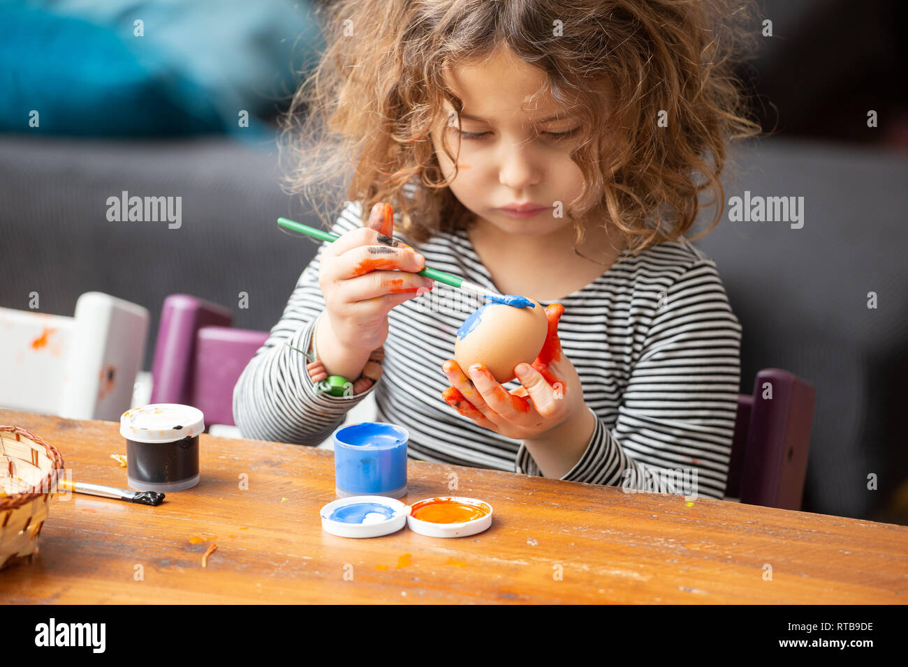 Toddler girl painting egg at table - Stock Image