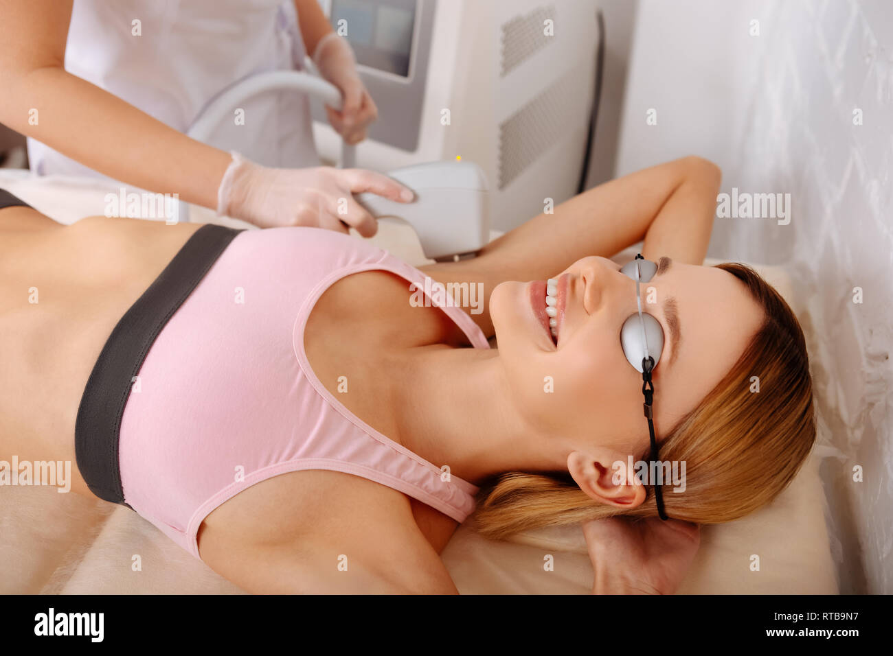 Blonde-haired woman feeling satisfied while having photo hair removal - Stock Image
