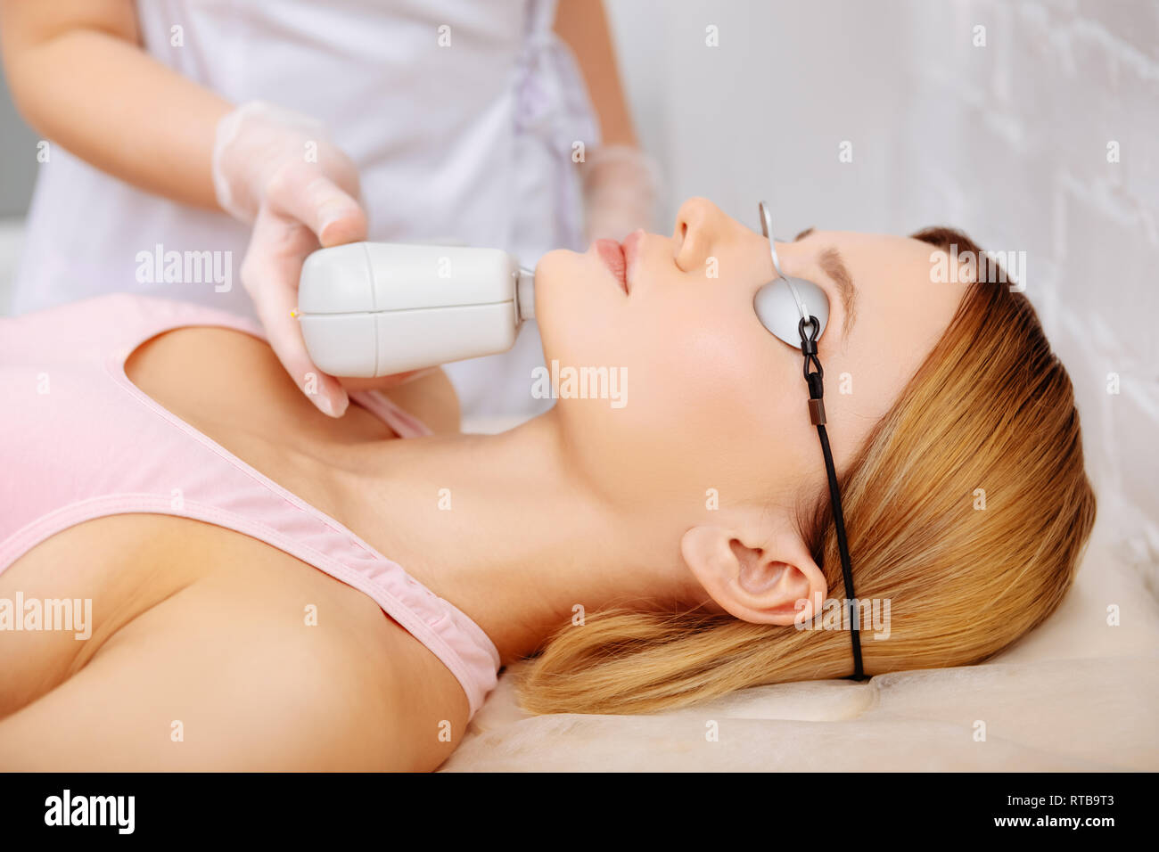 Woman wearing protective glasses making photo depilation of chin - Stock Image