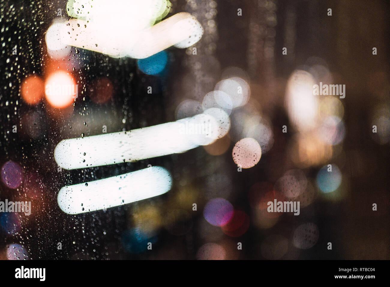 Night city through wet glass - Stock Image