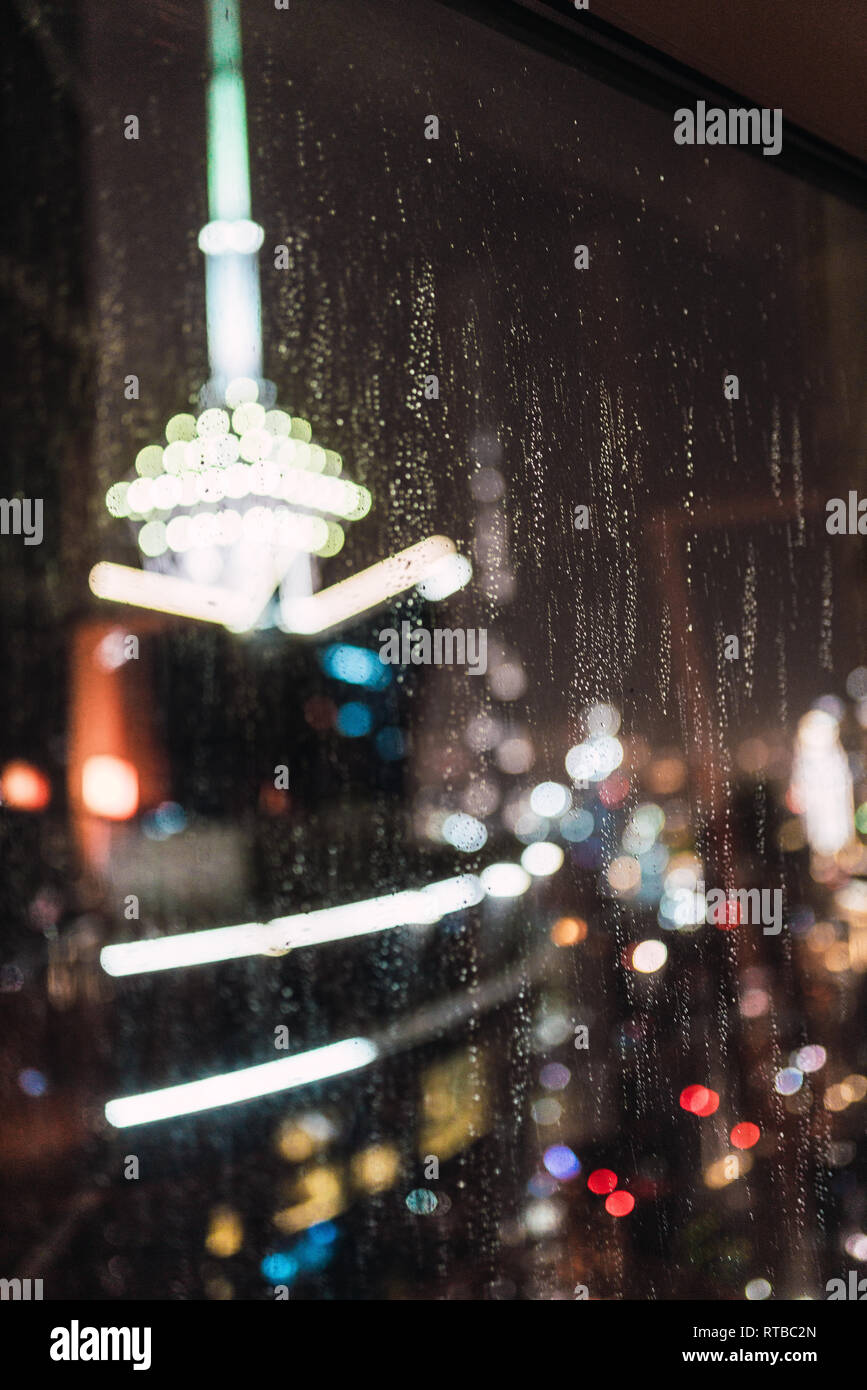 Blurred view of brightly illuminated modern city through wet window glass at rainy night in Dubai - Stock Image