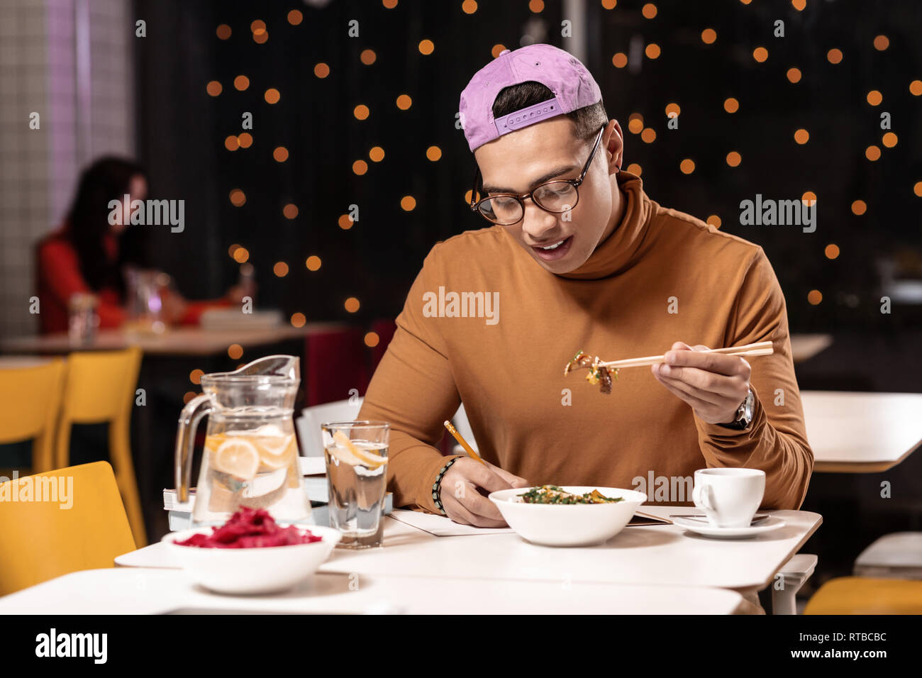 Customer feeling unhappy about ordered dish in restaurant and holding it with chopsticks. - Stock Image