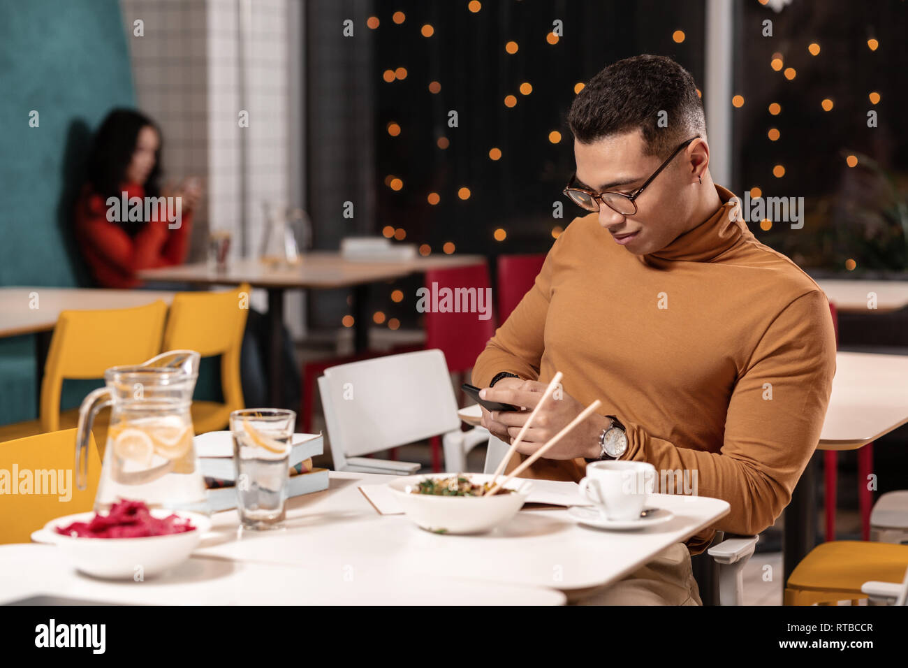 Man refusing to eat ordered dinner and chatting in the smartphone while sitting. - Stock Image