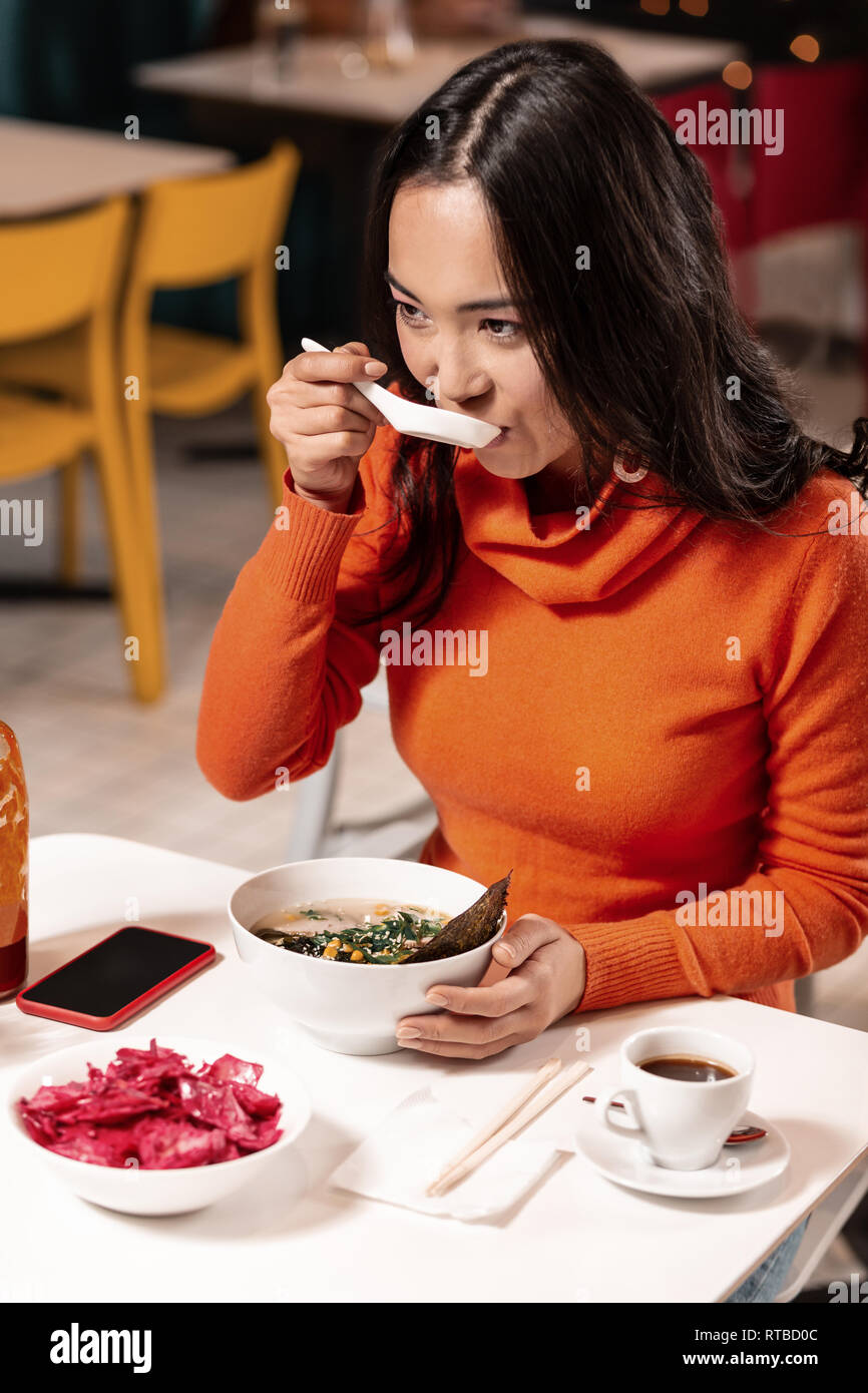 For the girl its more convenient having the ordered dinner with a spoon, not chopsticks. - Stock Image