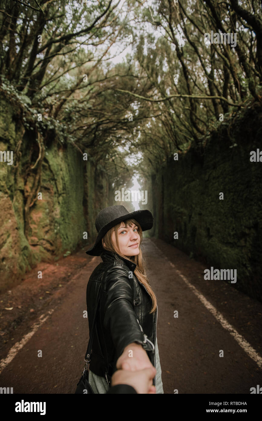 Side view of elegant lady in hat and leather jacket holding hand of person and standing on footpath between murk alley of high walls and woods - Stock Image