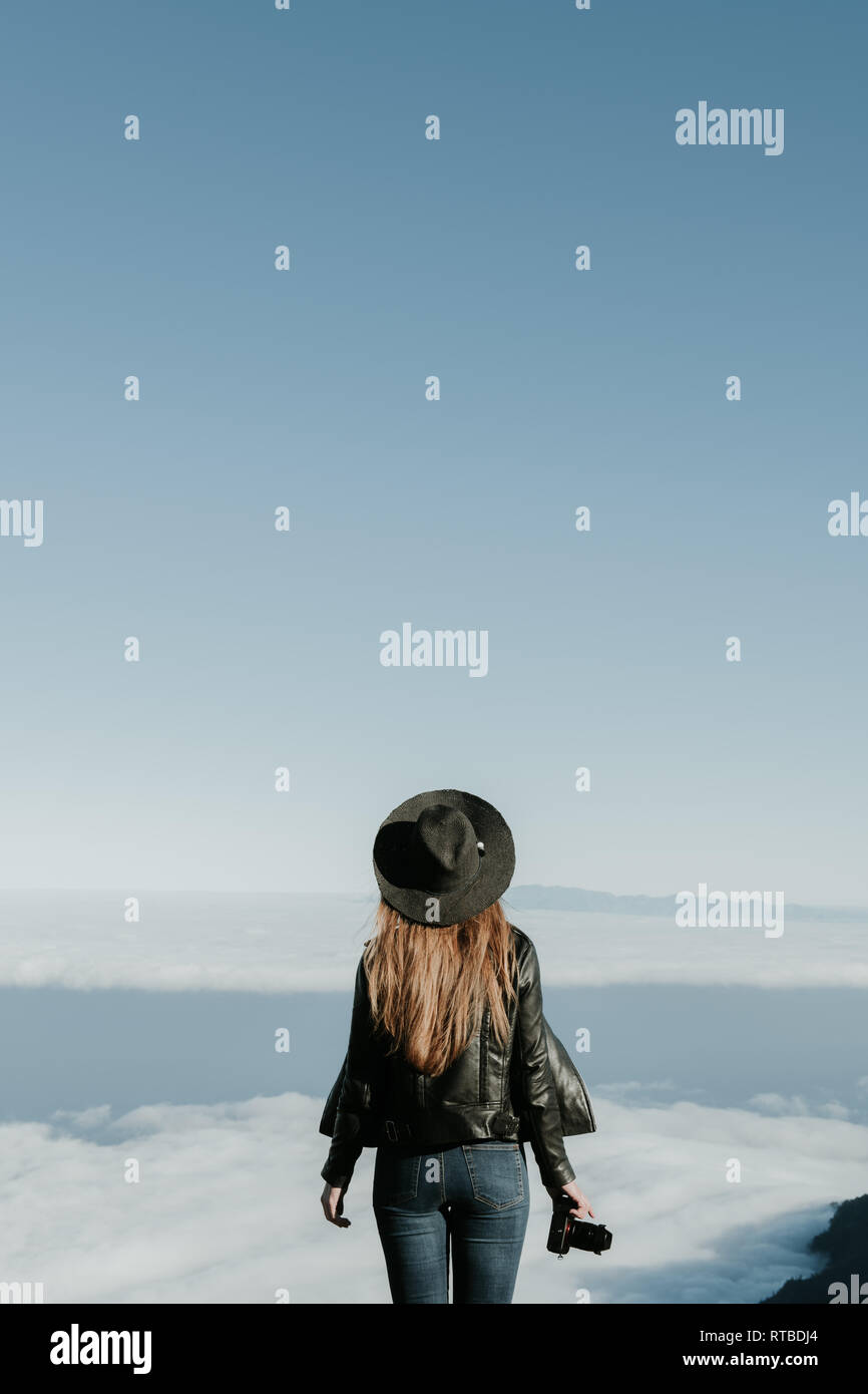 Back view of woman with photo camera standing on the top of the hill and looking at cloudscape - Stock Image