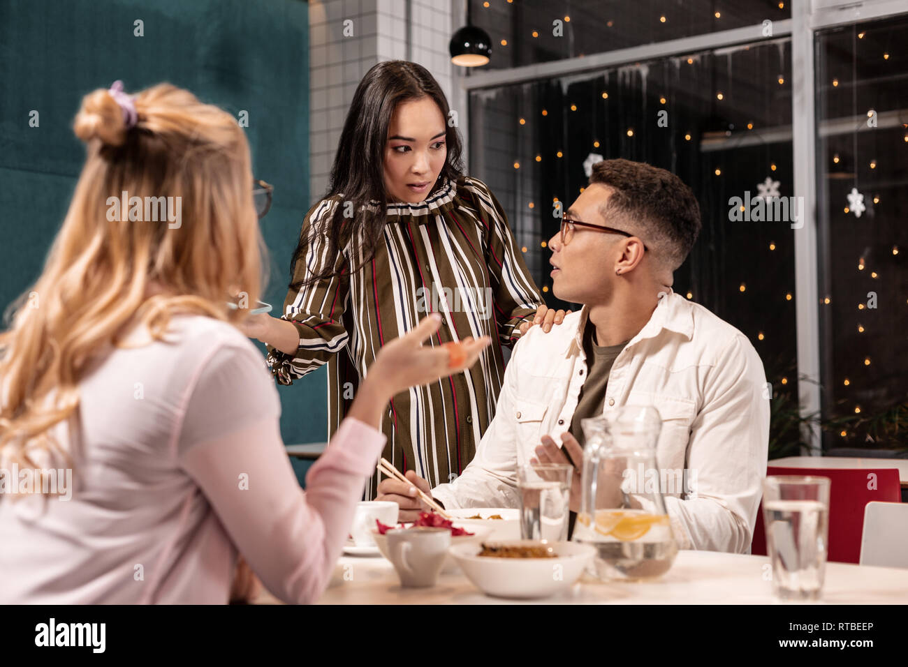 Girl feeling surprised and confused when seeing her boyfriend with another woman. - Stock Image