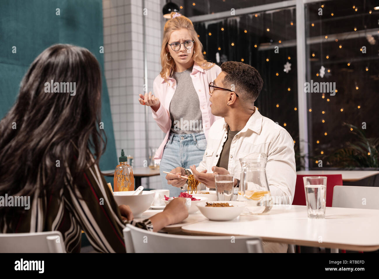 Young Caucasian woman arguing with her boyfriend while he sitting with another girl. - Stock Image