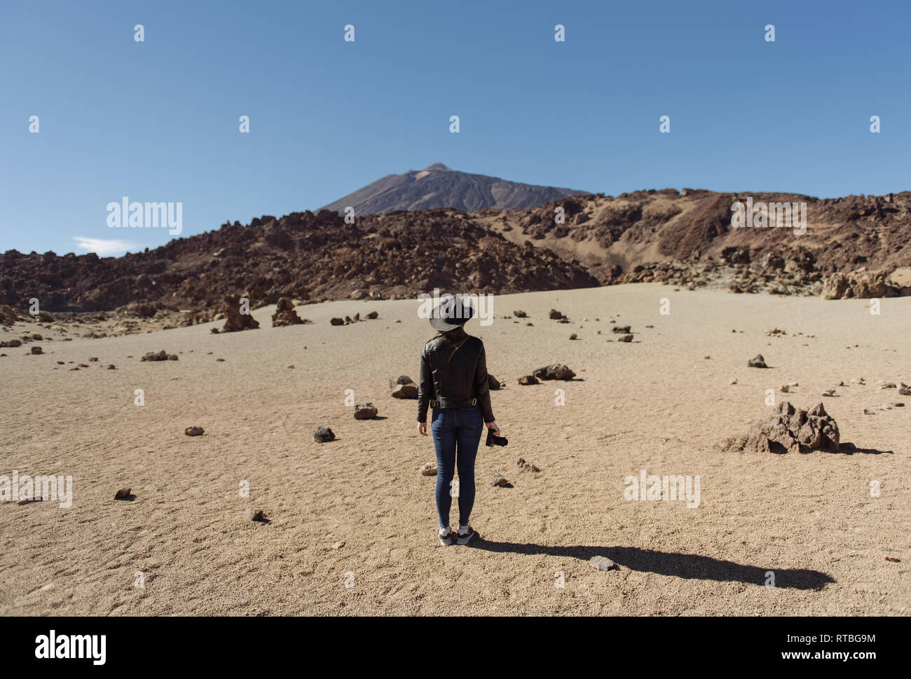 Back view of female photographer standing with camera and looking at hills in desert - Stock Image