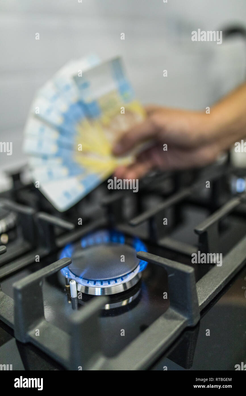 Cooktop with burning gas ring with hands holding money uah hryvnas for combustion . - Stock Image