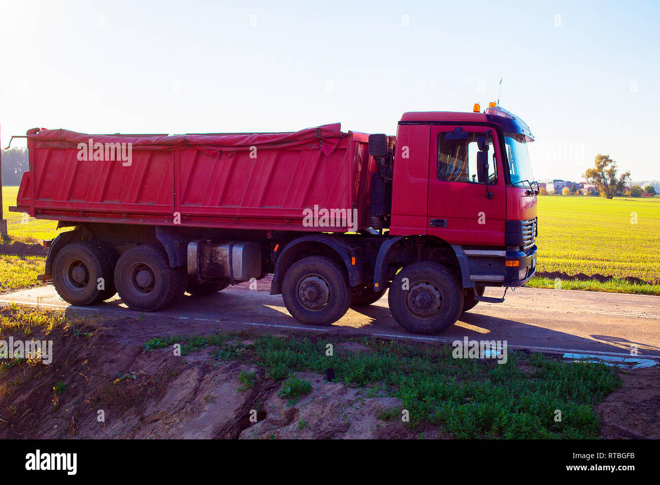 A red dump truck for sand delivery is parked with field and sky in the background - Stock Image