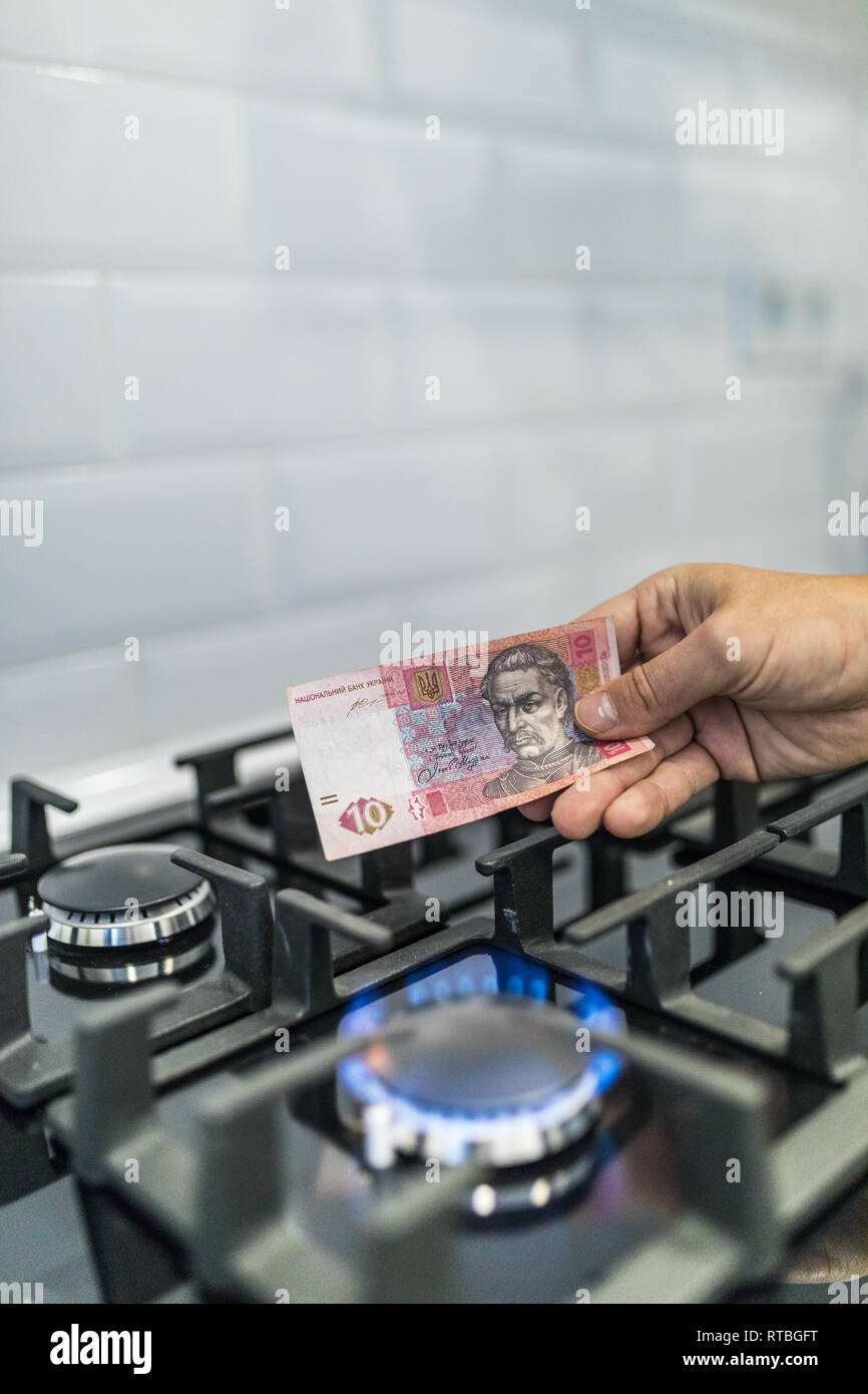 Cooktop with burning gas ring with hands holding money uah hryvnas for combustion at home. - Stock Image