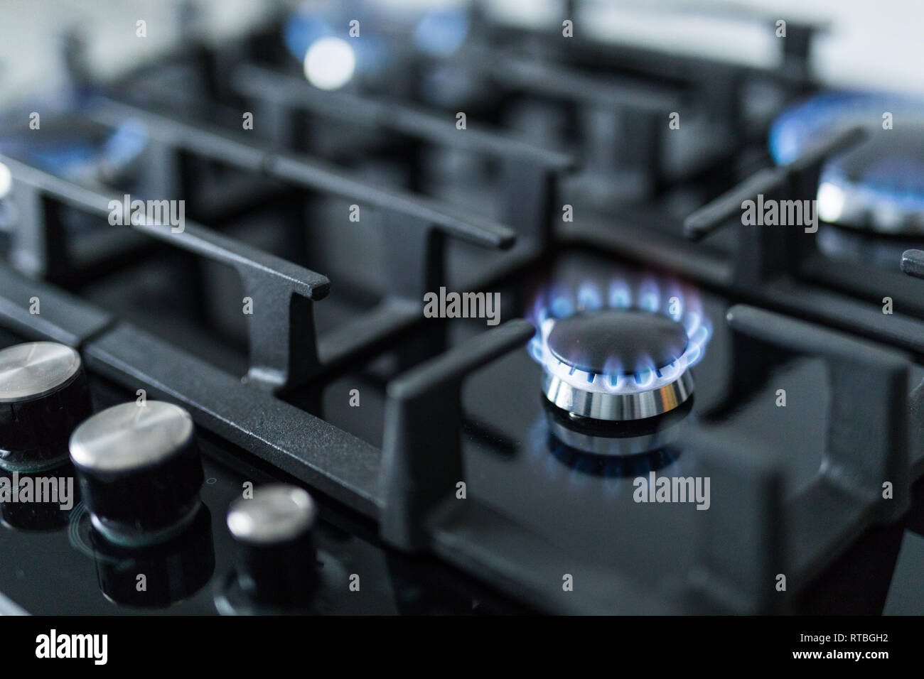 Cooktop with burning gas ring. Gas cooker with blue flames. Tinted photo. - Stock Image