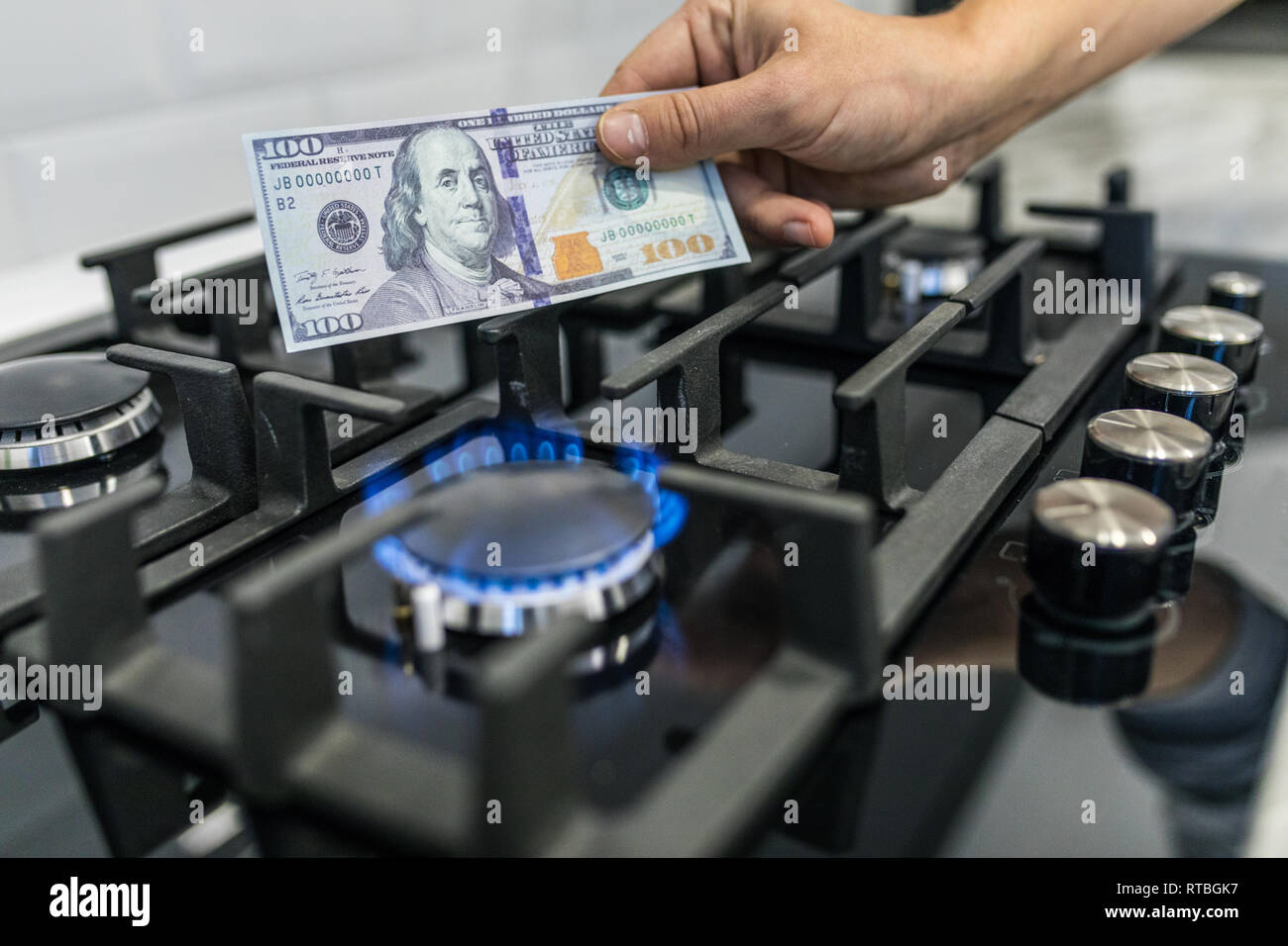Cooktop with burning gas ring with hands holding money 100 dollars for combustion - Stock Image