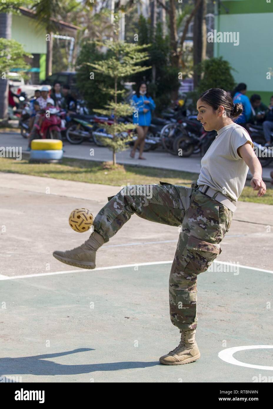 U.S. Army Spc. Erica Gonzales with 416th Civil Affairs Battalion (airborne) with Bravo Company, 5th Psychological Operations Battalion (airborne) participates in a game of Sepak Takrah at the Watjomthong School for the Annual Sports Day during exercise Cobra Gold 19, Phitsanulok, Kingdom of Thailand, Feb. 9, 2019. Cobra Gold is one of the largest theater security cooperation exercises in the Indo-Pacific and is an integral part of the U.S. commitment to strengthen engagement in the region. Cobra Gold 19, the 38th interation of this exercise, emphasizes coordination on civic action, such as hum - Stock Image