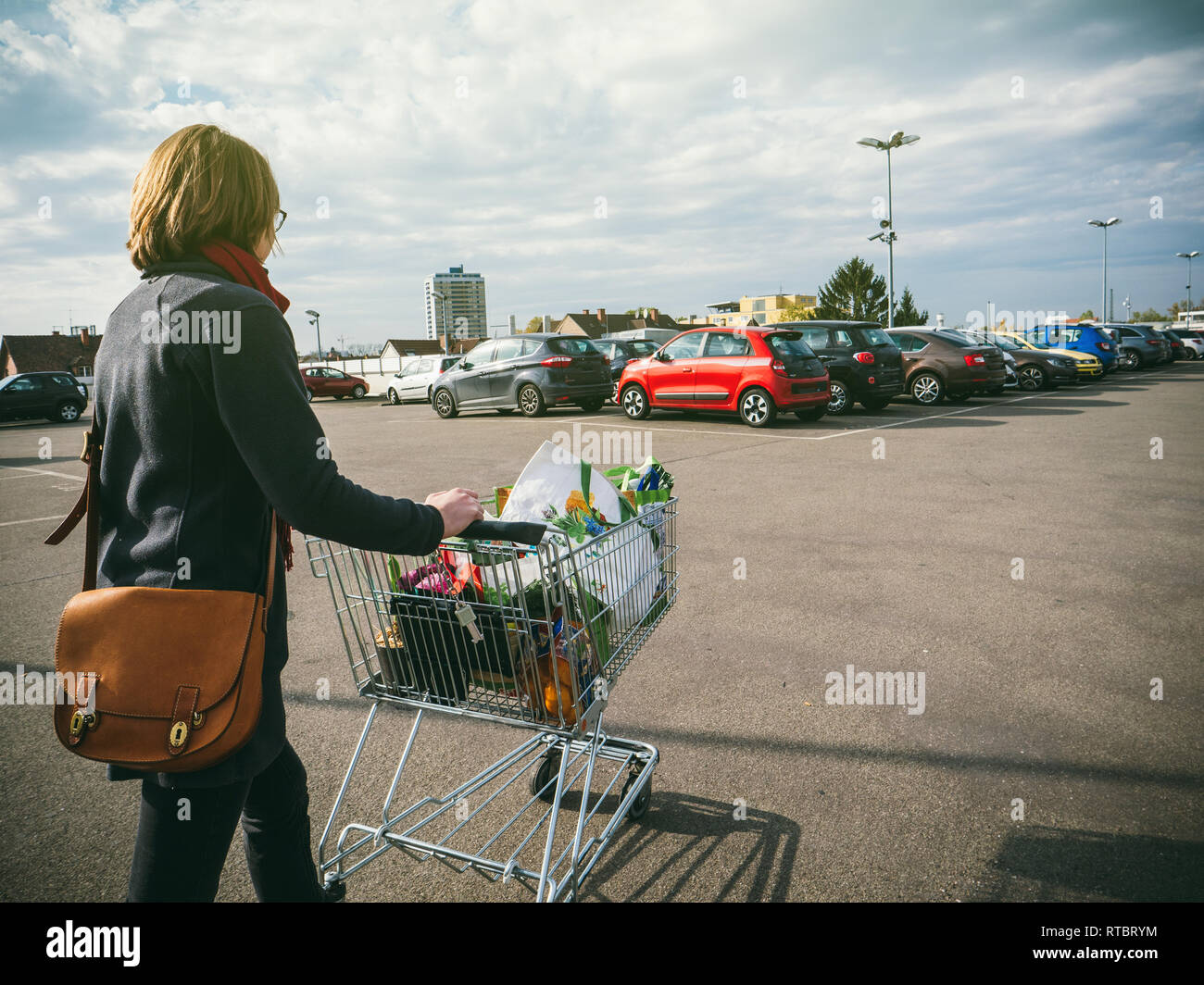 Woman pushing supermarket cart full with food and household products tot he car parked on the roof parking - Stock Image