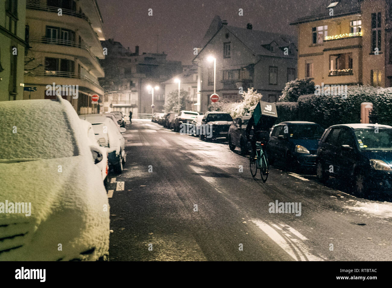 STRASBOURG, FRANCE - DEC 3 2017: Deliveroo delivery employee on bike in French city cycling fast for food delivery on time on a cold winter snowy night in residential neighborhood with cars parked - Stock Image