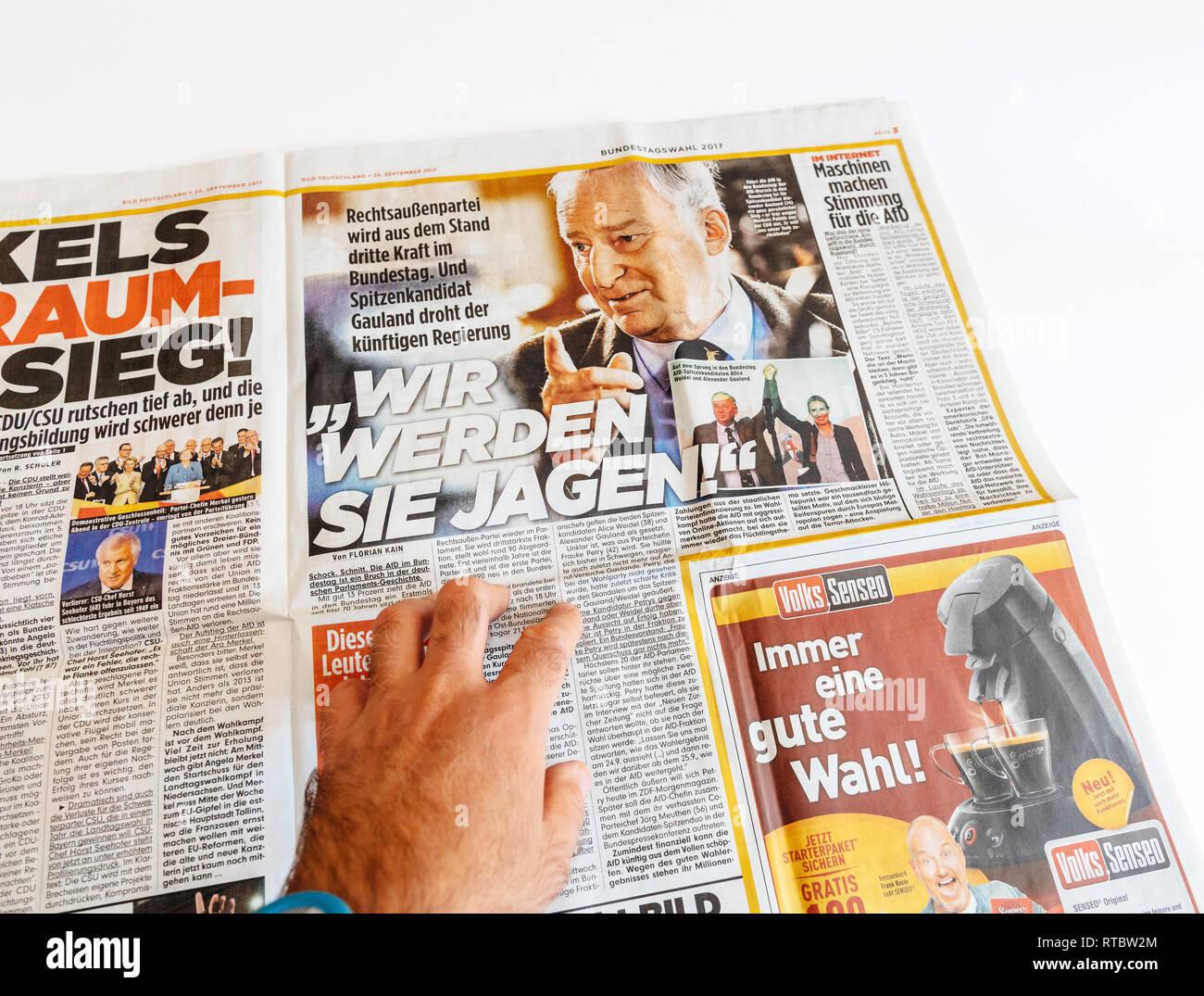 PARIS, FRANCE - SEP 25, 2017: Man reading French Die Bild  with Jorg Meuthen, Alice Weldel, Alexander Gauland photos from Alternative fur Deutschland political party newspaper election Germany  - Stock Image