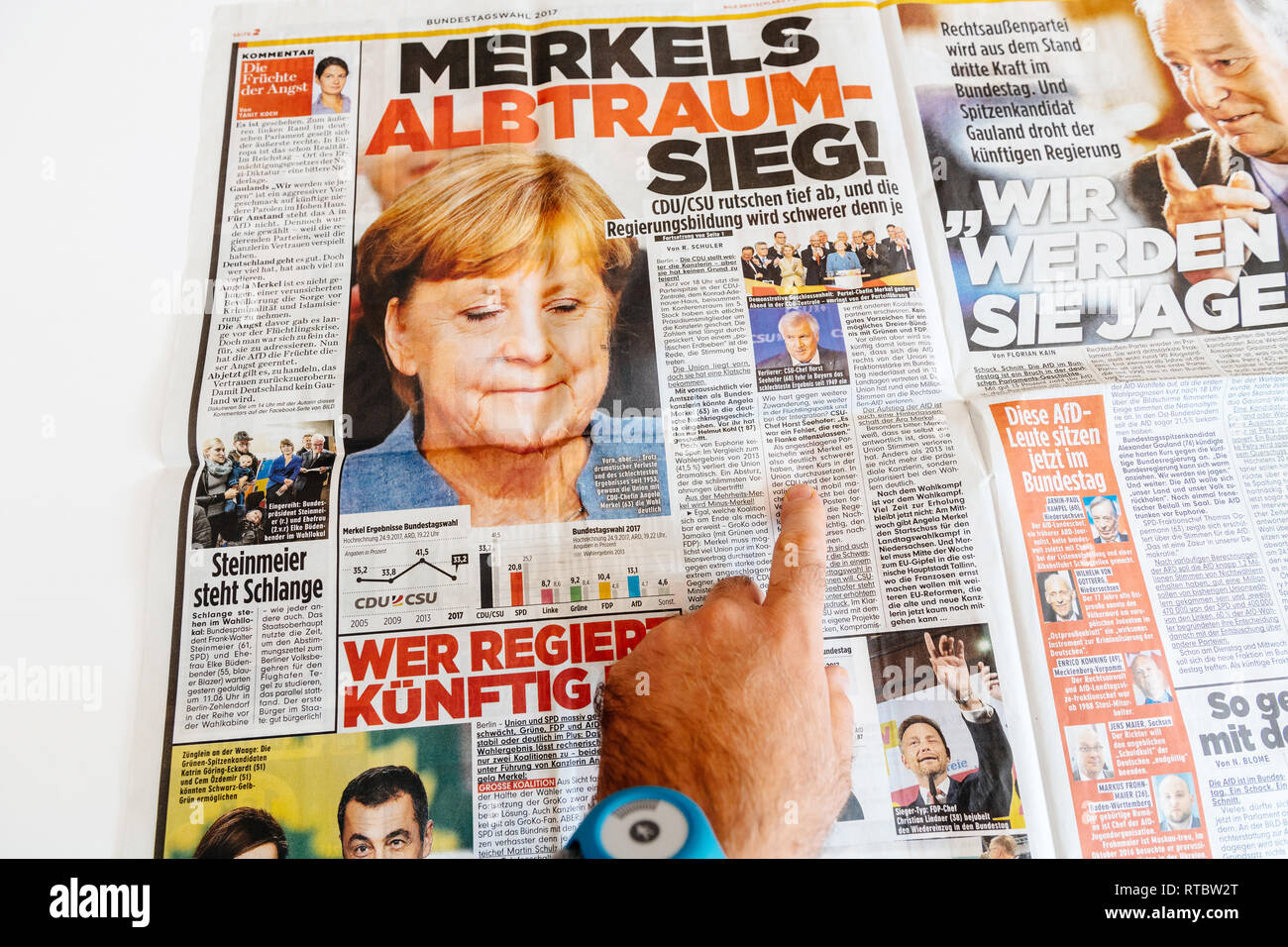 PARIS, FRANCE - SEP 25, 2017: Die Bild german newspaper man reading with portrait of Angela Merkel after election in Germany for the Chancellor of Germany, the head of the federal government - Stock Image
