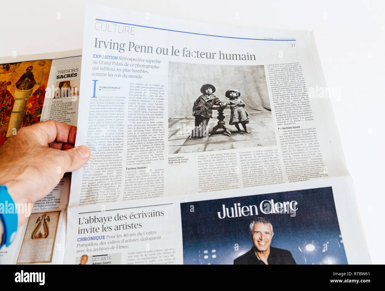 PARIS, FRANCE - SEP 25, 2017: Man reading international newspaper about Irving Penn exibition at Grand Palais in Paris, France  - Stock Image