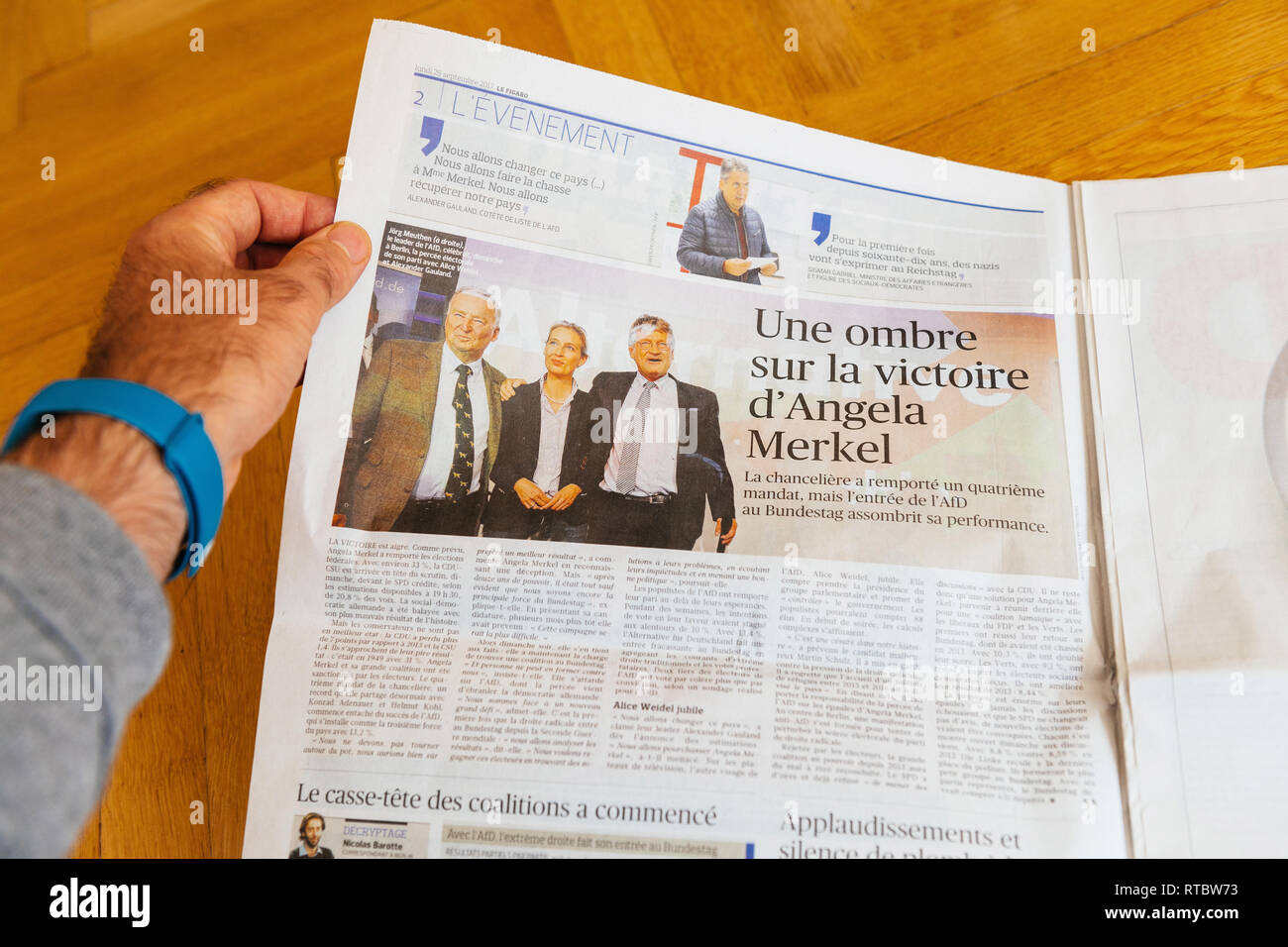 PARIS, FRANCE - SEP 25, 2017: Man reading French Le Figaro with Jorg Meuthen, Alice Weldel, Alexander Gauland photos from Alternative fur Deutschland political party newspaper election Germany  - Stock Image