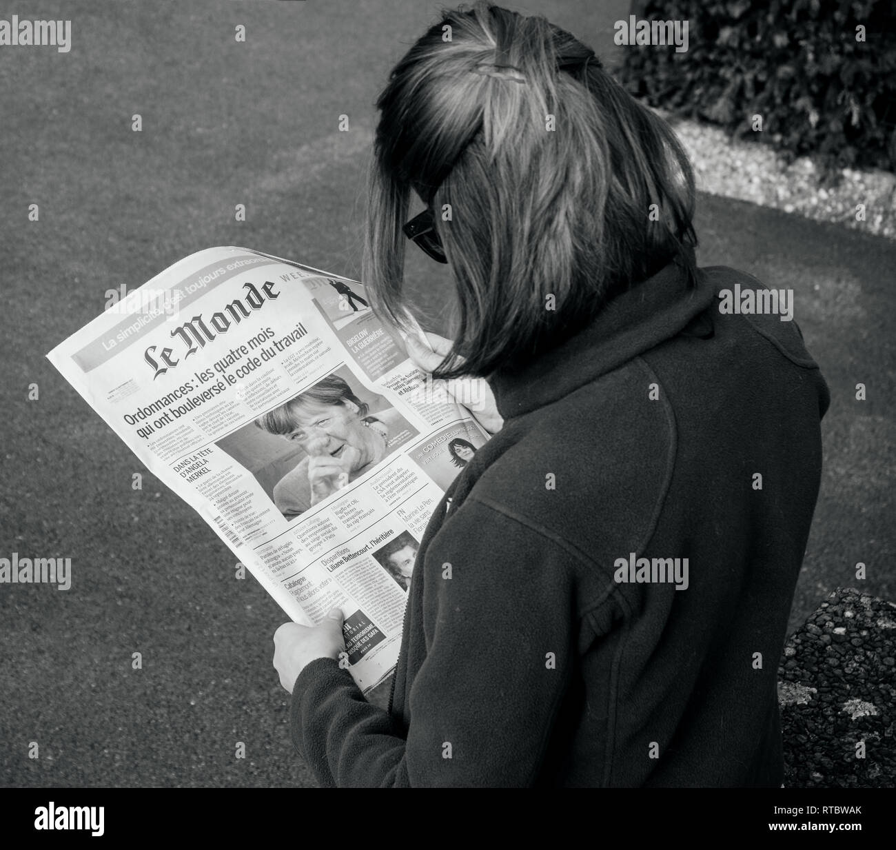 PARIS, FRANCE - SEP 24, 2017: View from above of woman reading latest newspaper Le Monde with portrait of Angela Merkel before the election in Germany for the Chancellor of Germany, the head of the federal government - Stock Image