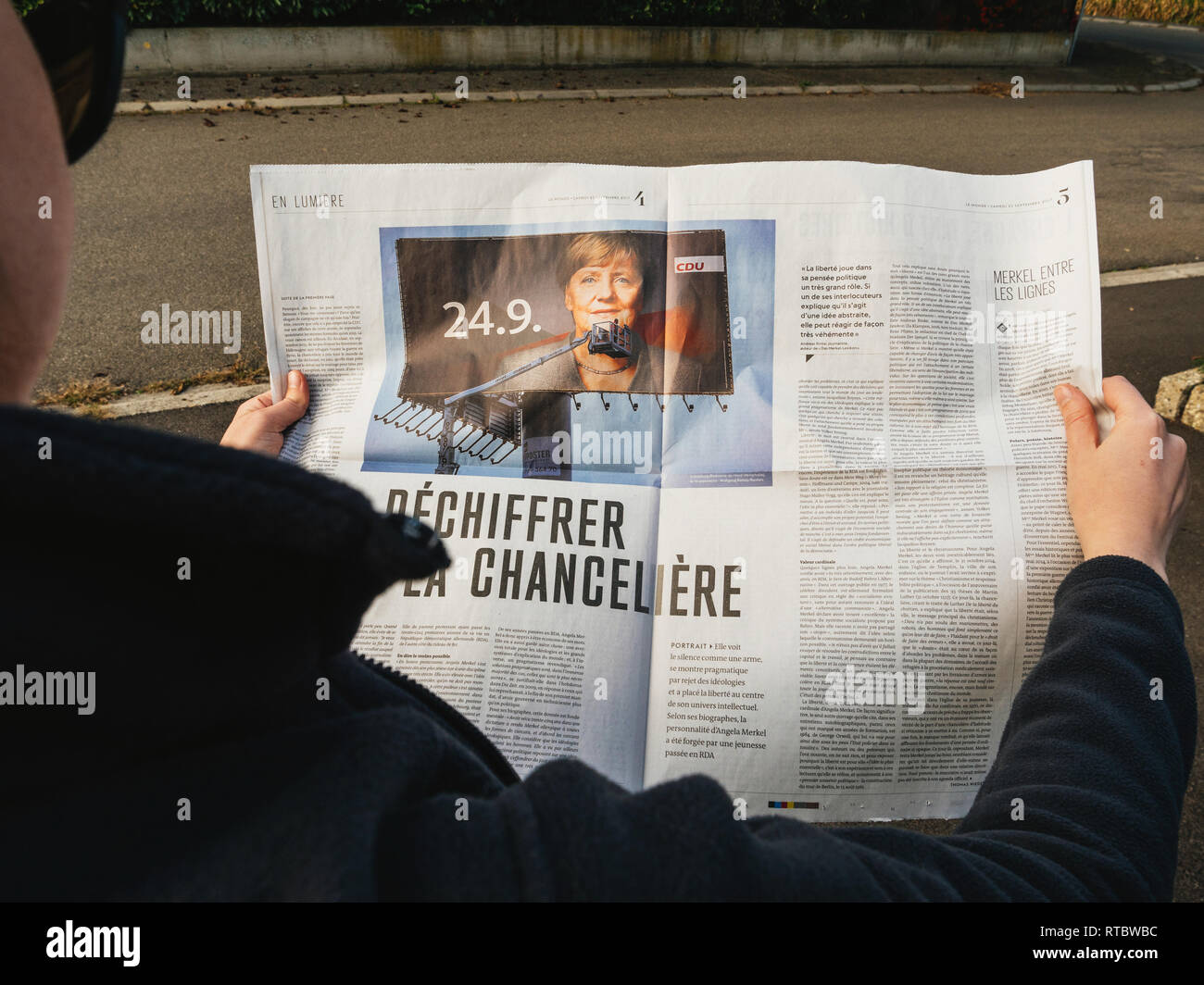 PARIS, FRANCE - SEP 24, 2017: Side view of woman reading latest newspaper Le Monde with article investigation about Angela Merkel before the election in Germany for the Chancellor of Germany, the head of the federal government - Stock Image