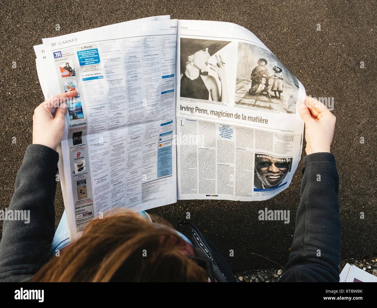 PARIS, FRANCE - SEP 25, 2017: Woman reading international newspaper about Irving Penn exibition at Grand Palais in Paris, France  - Stock Image