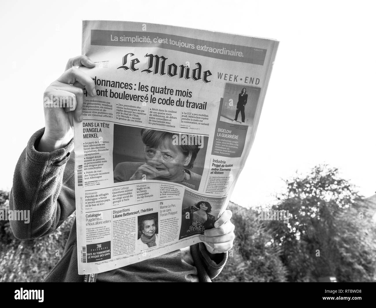PARIS, FRANCE - SEP 24, 2017: View from below of woman reading latest newspaper Le Monde with portrait of Angela Merkel before the election in Germany for the Chancellor of Germany, the head of the federal government Stock Photo