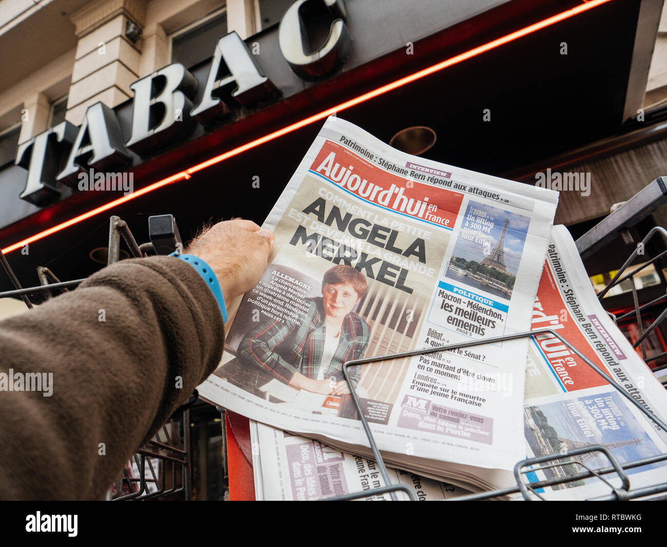 PARIS, FRANCE - SEP 23, 2017: Man buying latest French Aujord'hui newspaper with portrait of young Angela Merkel before the election in Germany for the Chancellor of Germany, the head of the federal government, currently Angela Merkel - Stock Image