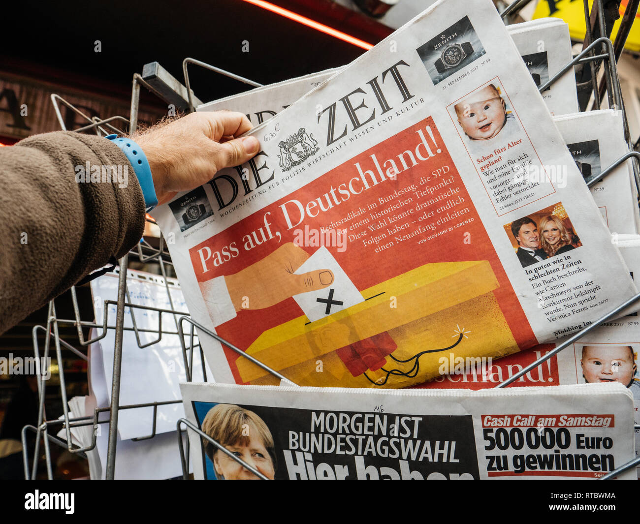 PARIS, FRANCE - SEP 23, 2017: Man buying latest newspaper Die Zeit German press with portrait of Angela Merkel before the election in Germany for the Chancellor of Germany, the head of the federal government, currently Angela Merkel - Stock Image