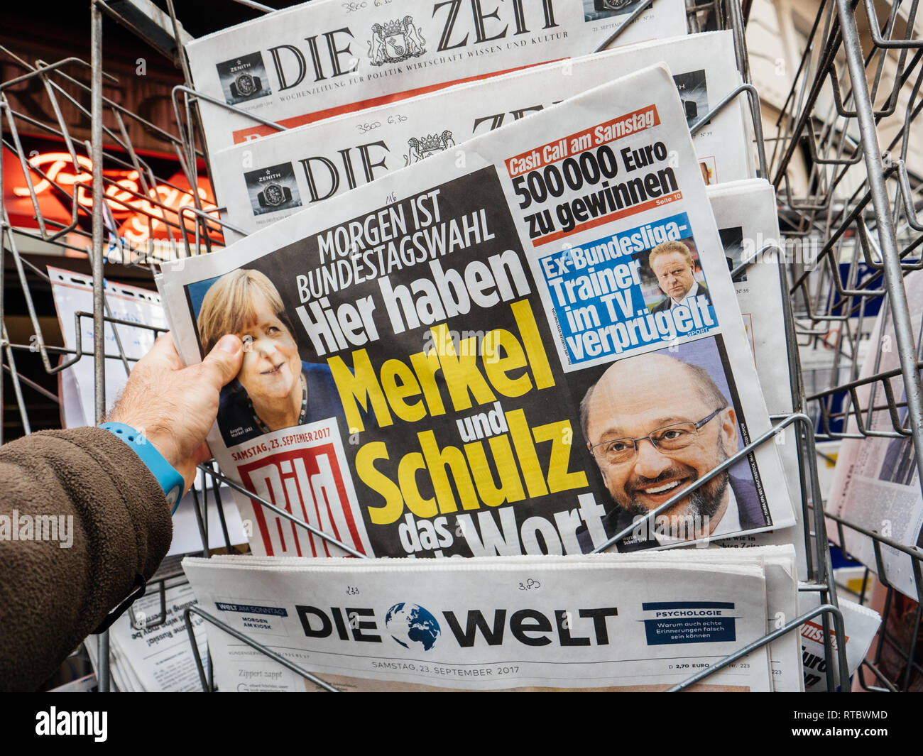 PARIS, FRANCE - SEP 23, 2017: Man buying latest newspaper Die Bild with with portrait of Angela Merkel And Martin Schulz before the election in Germany for the Chancellor of Germany, the head of the federal government, currently Angela Merkel - Stock Image