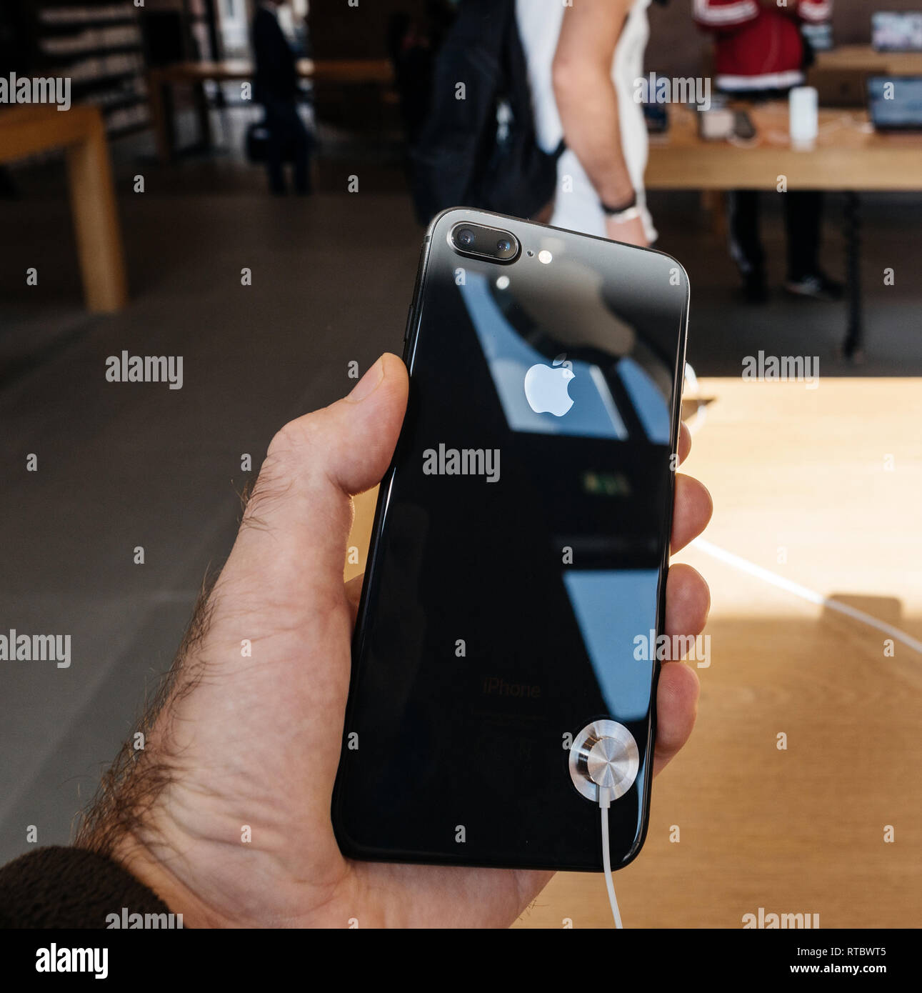 PARIS, FRANCE - SEP 22, 2017: New iPhone 8 and iPhone 8 Plus, as well the updated Apple Watch, Apple TV goes on sale today in Apple Store with customer holding the phone looking at the glass body  Stock Photo