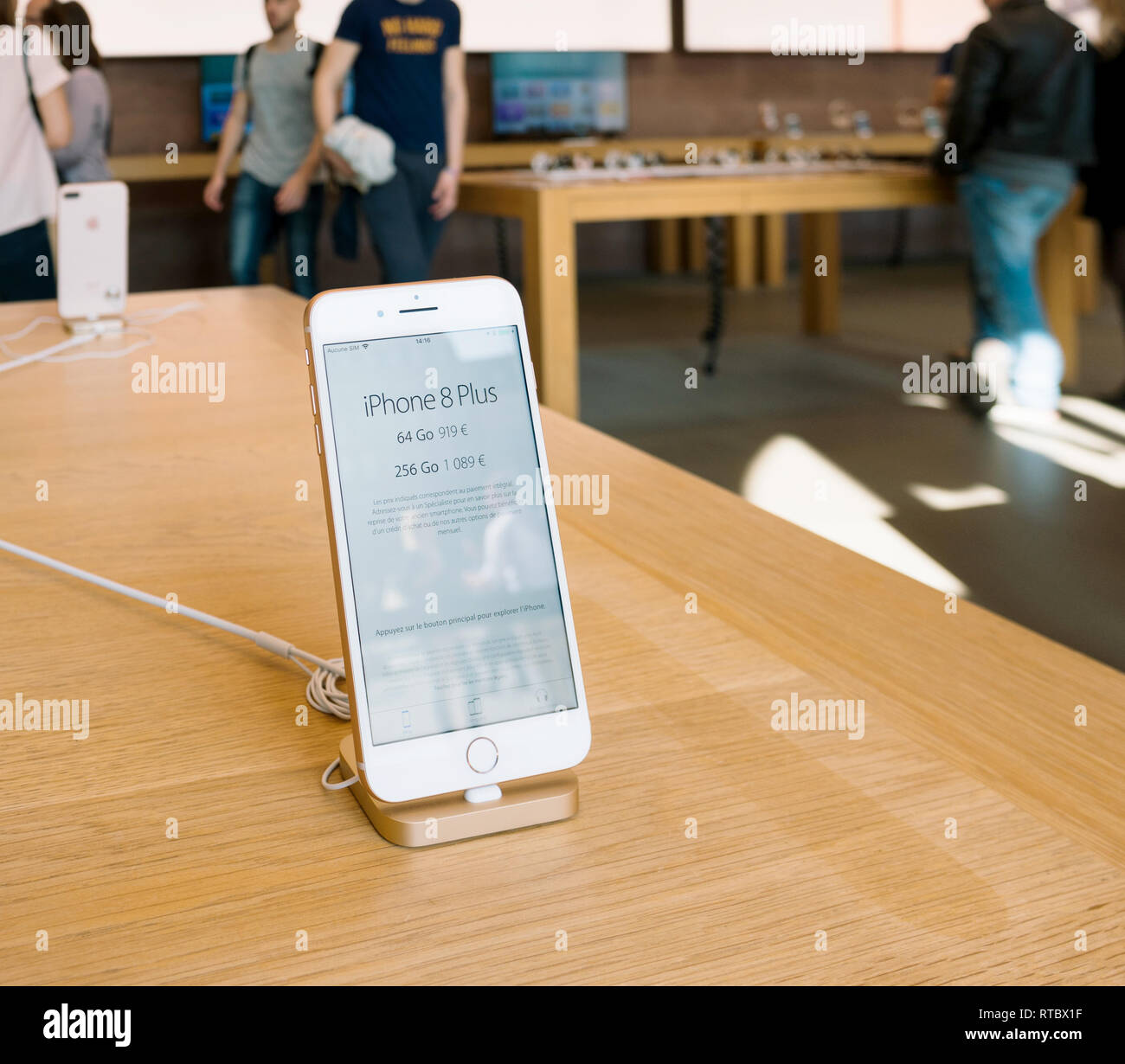 PARIS, FRANCE - SEP 22, 2017: New iPhone 8 and iPhone 8 Plus, as well the updated Apple Watch, Apple TV goes on sale today in Apple Store with phone on the wooden table  Stock Photo