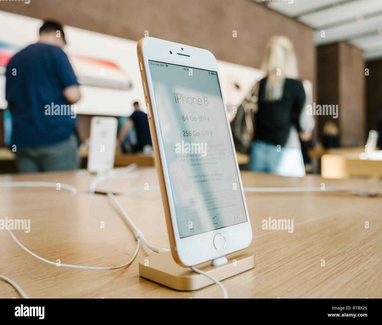 PARIS, FRANCE - SEP 22, 2017: New iPhone 8 and iPhone 8 Plus, as well the updated Apple Watch, Apple TV goes on sale today in Apple Store with customers silhouette in background  Stock Photo