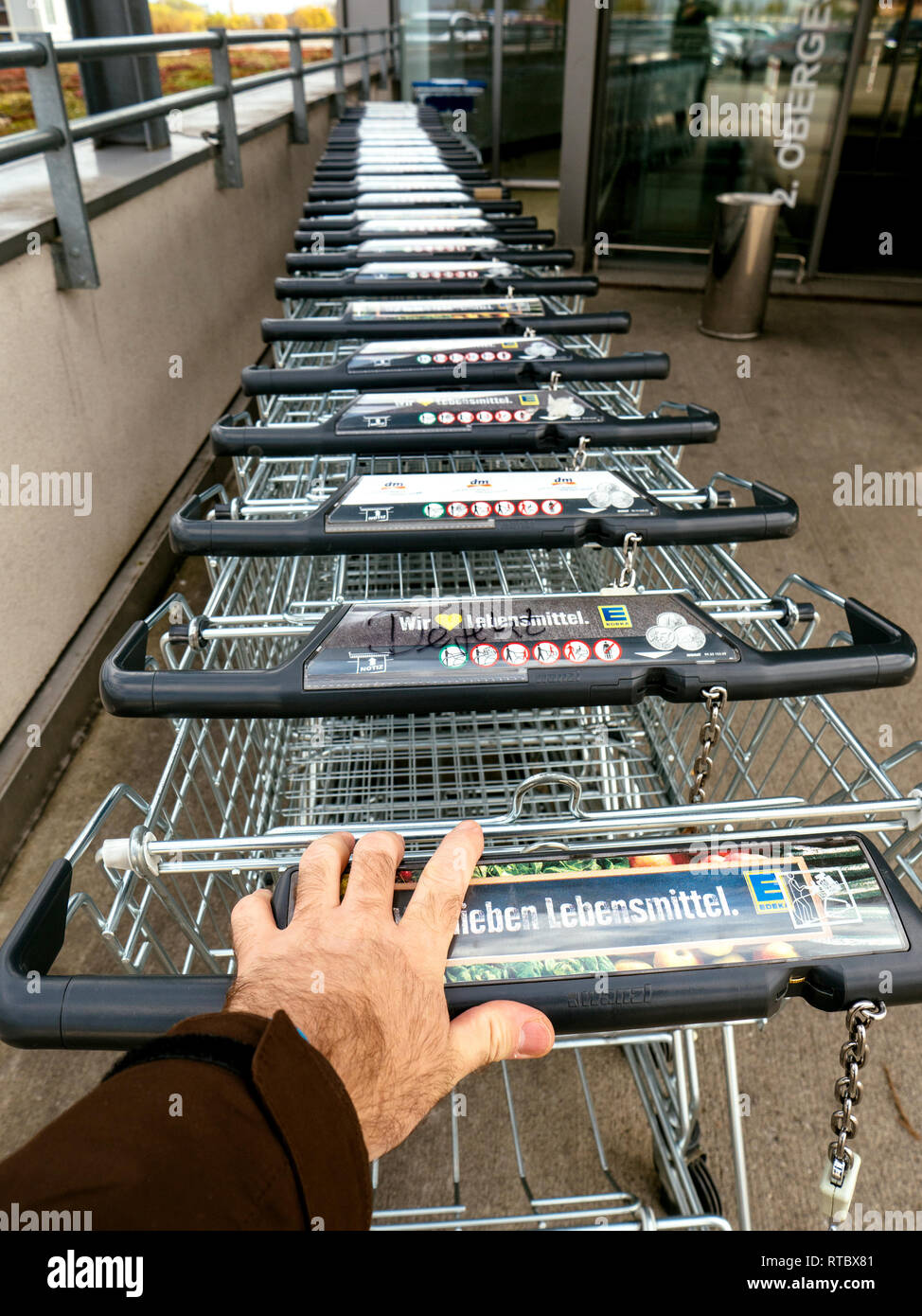 FRANKFURT, GERMANY - NOV 4, 2017: Man hand POV over the WANZL supermarket cart in front of the entrance with Eingang sign to the Edeka store - paying for the rent of the cart  - Stock Image