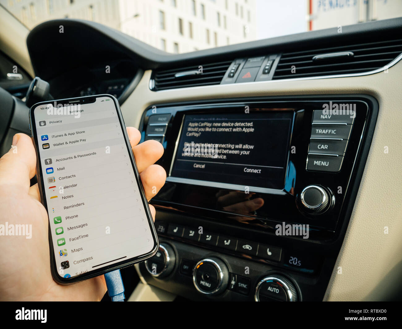 FRANKFURT, GERMANY - NOV 4, 2017: Man connecting his new iPhone X 10 to the navigation system of the car with CarPlay - message on GPS - new device detected  - Stock Image
