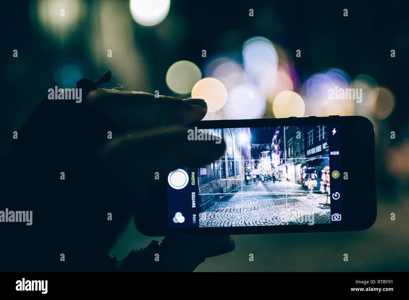 STRASBOURG, FRANCE - NOV 21, 2017: POV Tourist hand holding Apple iPhone smartphone in hand taking photographs of the Christmas Decorations of Christmas Market in Strasbourg - blue cold tones  - Stock Image