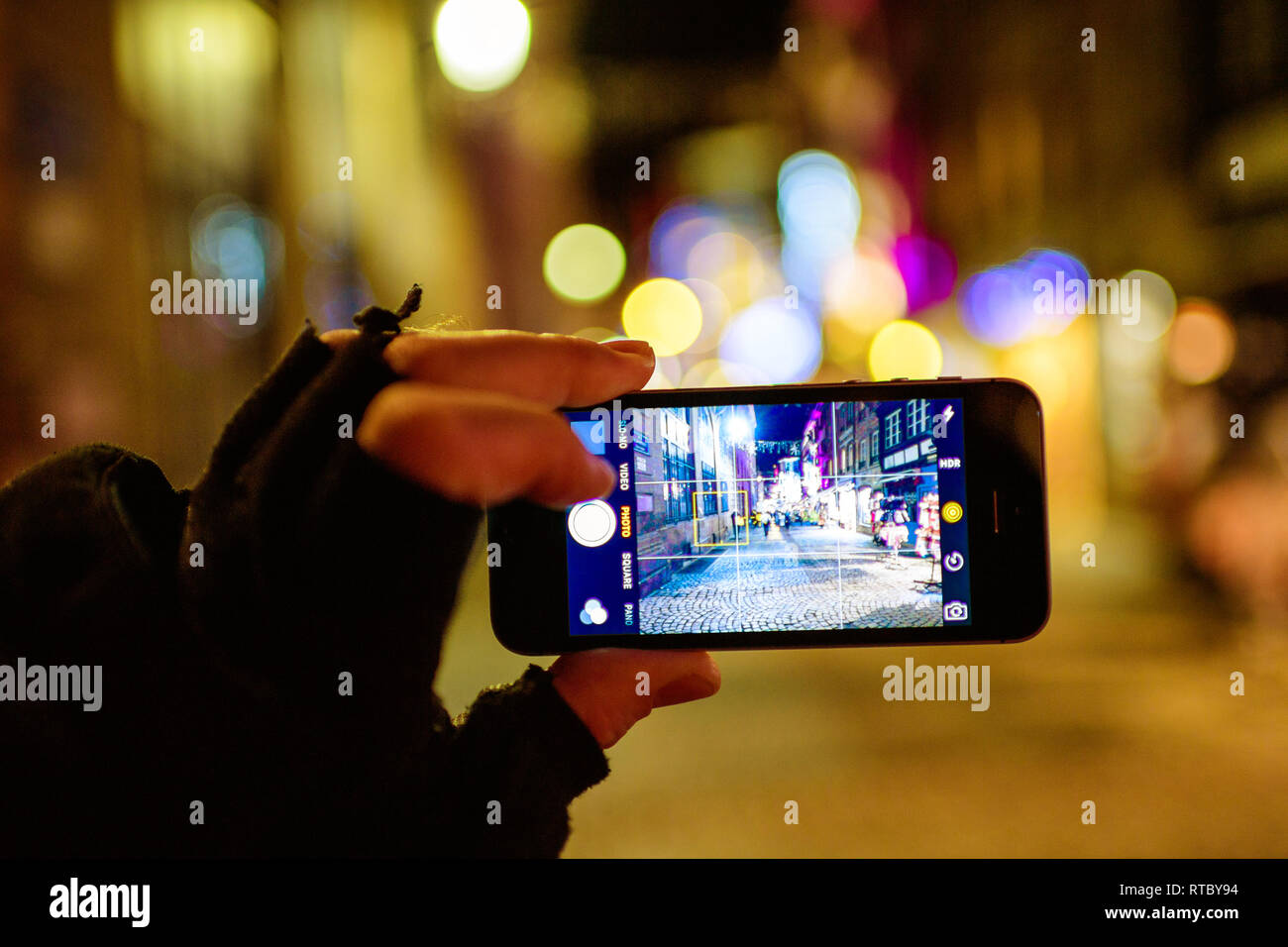 STRASBOURG, FRANCE - NOV 21, 2017: POV Tourist hand holding Apple iPhone smartphone in hand taking photographs of the Christmas Decorations of Christmas Market in Strasbourg - Stock Image