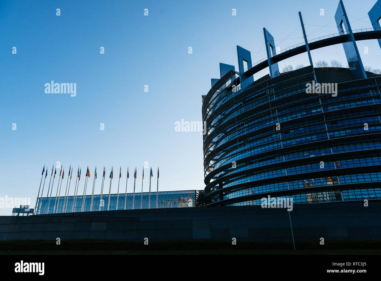 STRASBOURG, FRANCE - APR 6, 2018: Side view of European Parliament building in Strasbourg with all European Union flags waving at sunrise - Stock Image