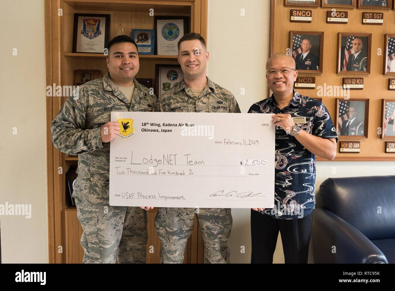U.S. Air Force Tech. Sgt. Christopher Sills, 18th Communication Squadron programmer, Staff Sgt. Alexander Nestle, 18th CS software development supervisor, and Bernard Obsuna, 18th Force Support Squadron information technology chief, pose for a photo with their 2018 Shogun Spark Tank check on Feb. 11, 2019 at Kadena Air Base, Japan. Innovative incentive programs such as the 18th WG Spark Tank encourage Airmen to think outside the box and provide new solutions to everyday problems. - Stock Image