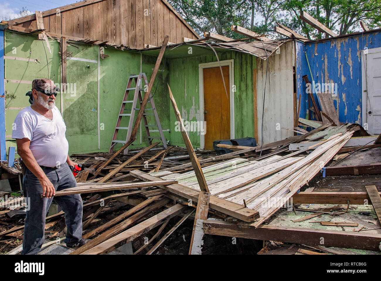 Joe Guerra talks to a neighbor as he clears rubble from his storm-damaged home after Hurricane Harvey, Oct. 4, 2017, in Refugio, Texas. - Stock Image