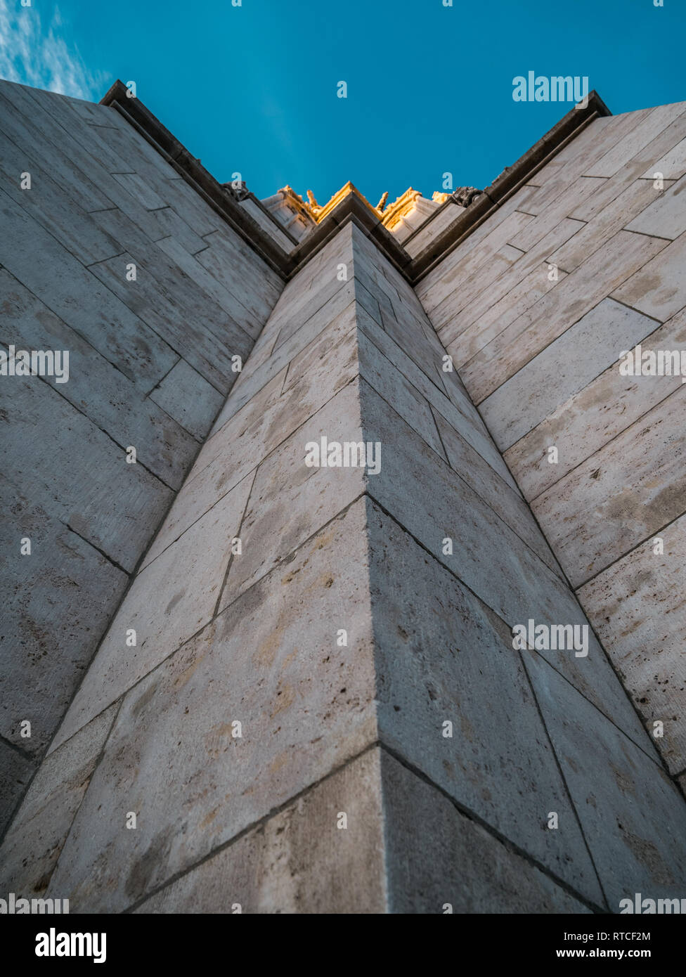 Image of bottom up view along a wall of a tower with golden top in budapest - Stock Image