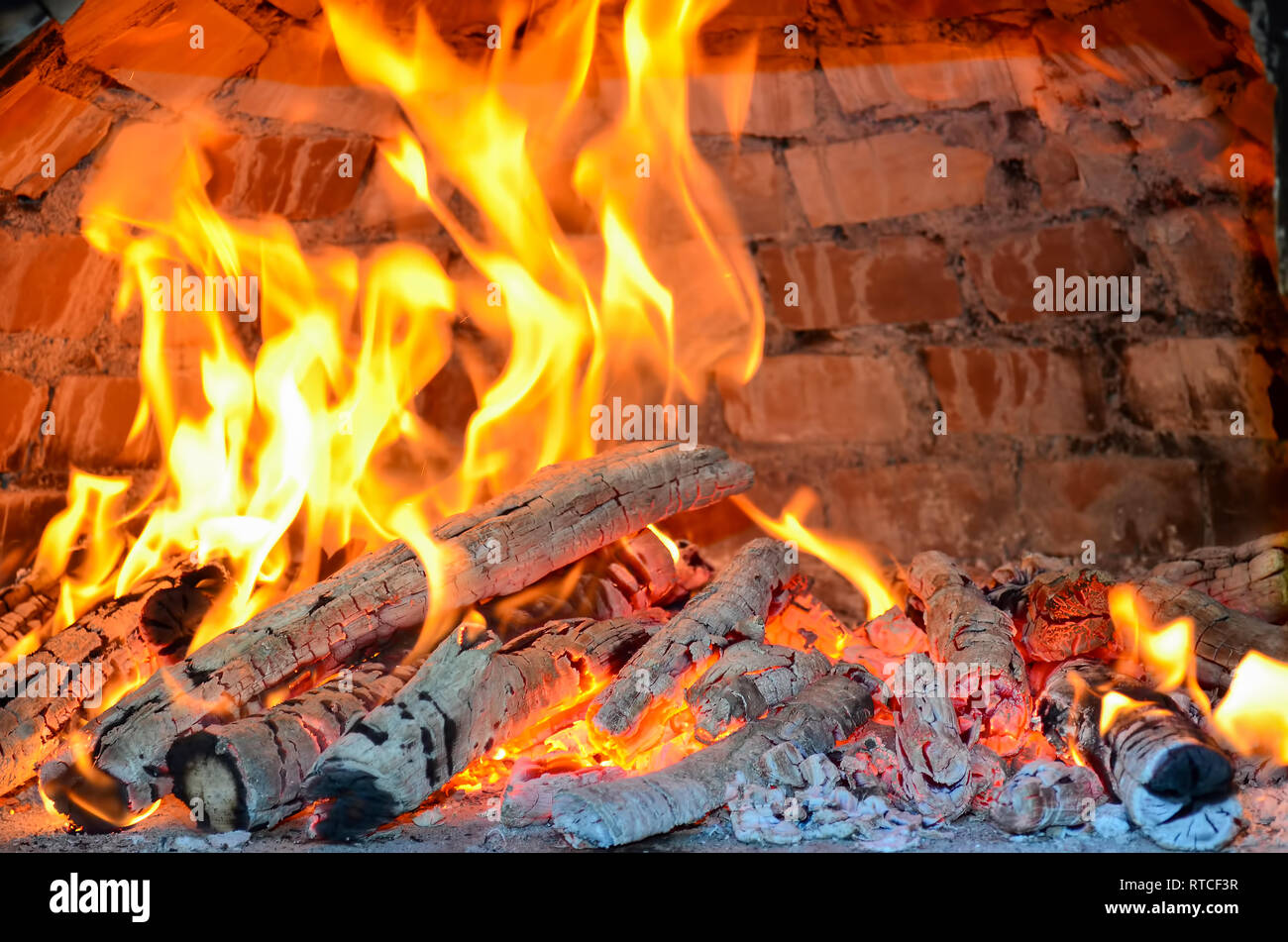 Pizza oven heating by burning beech and birch firewood providing high temperature and special smell, almoust done - Stock Image